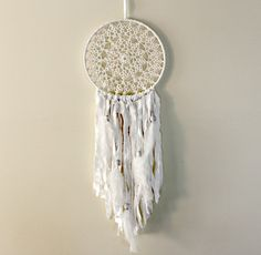 Large white dreamcatcher with white feathers    Measures 9.5 across by 35 long including cotton hanger    The center is an intricate off-white