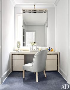 A nook in the couple's dressing area with a custom-made mirror and vanity and a slipper chair | archdigest.com