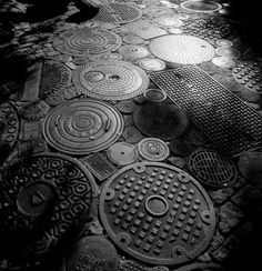 A collection of manhole covers from the scrapyards of Los Angeles, spread out on an immense driveway amongst cobblestones and bricks