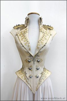 "Couture Corset ""The Admiral""""The Admiral"" is a uniform inspired corset top with high collar, lapels, spikey epaulettes and semi-transparent detachable skirt pieces.The corset is made from satin and is elaborately decorated with lace appliqué, synthetic leather cutwork, silver beads, Swarovski crystals and metal buttons.The epaulettes are made from sturdy thermoplast and are also decorated with beads, Swarovski crystals and buttons.(x) WOW!"