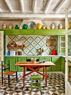 Spanish home: Colourful, continental kitchen with decorative tiles and bright green cupboards.