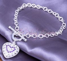This darling bracelet has a high polish, bright silver plated chain and heart charm. This puff heart charm has micro pave White and Tanzanite CZ stones with a toggle closure. 8 inches.