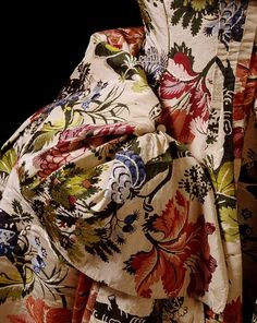 Mantua, England, 18th Century. Brocaded silk, hand-sewn with spun silk and spun threads, lined with linen, brown paper lining for cuffs, brass, canvas and pleated silk detail, Victoria & Albert Museum