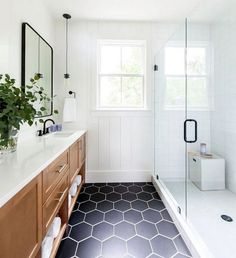 Can we talk about how gorgeous this bathroom is? We love the combination of white walls, black hex tiles and wood cabinetry! For more hexagon tile inspiration head to the website. Design by Photo by Bathroom Floor Tiles, Bathroom Renos, Black Bathroom Floor, Wood Tile Bathrooms, Rain Shower Bathroom, Tile Floor, Black And White Tiles Bathroom, Bathroom Fixtures, Pavillion