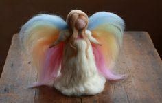 Un ángel muy encantador con alas de color arco iris. Un portador de luz, desde el reino celestial. Ella camina a través del majestuoso arco del