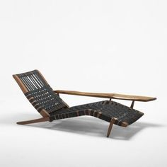 A 1951 George Nakashima Long chair made of black walnut and canvas.