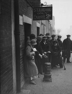 Arsenal fans getting warm from a stove while queuing at the Highbury stadium for tickets to see the match against Chelsea and the ceremony to open the new covered stands which will be attended by the Prince of Wales, 16th December 1932. (Photo by H. F. Davis/Topical Press Agency/Getty Images)