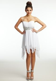 Be a divine diva in this pure white jersey dress. This party dress should be worn as a cocktail dress, graduation dress, as a pretty summer dress, or any formal occasion where you want to look fabulous! A ruched bodice with spaghetti straps makes for a classic look while a wide empire waistband spices up this design with dazzling jewels. The sheer hanky hem high-low skirt is a fun touch to this heavenly short dress and creates blissful movement as you party the night away! Couple this with…