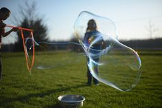 They made bubbles right out on the lawn at dusk.  As if you can lift the thin skin of things.  As if you can wait for the space between stillness and wind, and rise.                              Malakai, he wears faded jeans two inches too short, the hem just skimmi
