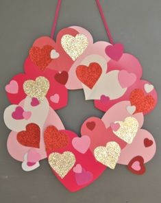 Nothing says #ValentinesDay like a #wreath full of #hearts! #Glitter -ing construction paper makes this decoration really shine. #crafts #kids