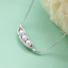 This is sweet pea necklace.  Three white pearls lay together as peas in a pod.......  A perfect gift for best friends or just a swe