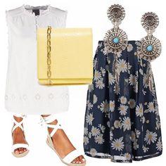 Gonna a vita alta blu con margherite, top bianco in pizzo, sandali di corda bianchi alla caviglia, borsa tracolla giallo chiaro e orecchini pendenti argento e azzurri.