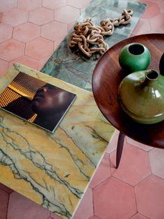 Garimpadas numa marmoraria, duas pedras em tons inusitados compuseram as mesinhas no estar. O modelo de madeira, dos anos 1950 (Loja Teo), completa o trio. O colar de barro foi comprado de uma artesã baiana.