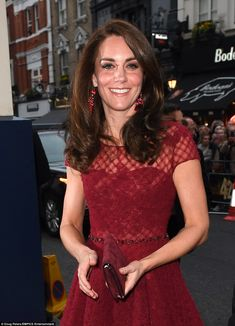 The Duchess added a pair of drop earrings to her scarlet ensemble, teaming the dress with red suede heels and a clutch