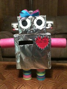 Robot Valentine box.  We used 2 small black olive cans for ears and 2 buttons for earrings.  A tuna can for hair and added a hair bow.  White and black construction paper for eyes.  4 vegetable cans for arms and legs.  Red card stock heart with bolts around it.  2 boxes and thick foil will also be needed.  I hot glued everything really well!