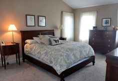 Bedroom with dark wood furniture, butterfly pillow and carpeting.
