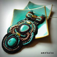 Náhrdelník, v jehož středu je použit tyrkys a keramický kabošon sv. modré barvy s praskanou glazurou, japonský TOHO a rokajl české výroby PRECIOSA, voskové perle a mačkané oválky.