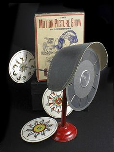 """""""Ludoscope Phenakistoscope""""   A variation, sometimes called a stroboscope, mounts the picture disk and the disk with slits separated on a spindle so that the pictures are viewed directly through the slits.    This early 20th century toy called a """"Motion Picture Show"""" or """"Ludoscope"""" came with its box with a set of disks on a red metal stand."""""""