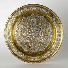 Made of heavy brass inlaid with silver and copper, decorated with interlacing patterns, tendrils and Islamic calligraphy inscriptions.