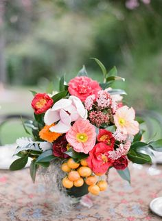 Pretty arrangement with fruit, nice variations of pinks/corals/peaches and a good blend of greenery. I wonder if we could include kumquats? Would that look good with the flower choices?