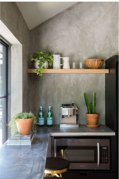 Dark gray kitchen with faux cement walls and open shelves