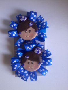 Coleteros azulones con base de lazo azulona con dibujitos blancos y aplique de carita en arcilla polimérica con moño lateral y adornos