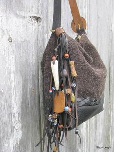 One of a kind leather bag in a furry brown suede and smooth black leather combination. The bag is 11 by 9 by 3 (nice petite size) with a black, embossed, vintage leather belt strap that adjusts from 20 to 24. The bag has a brass ring with a beaded, fringe tassel. The fringe has a genuine deer antler tip, whale bone bead, jasper stone, African trade beads, and other beads. The tassel is 5 oz. in weight with all the beads, but may be removed if you want to use the bag without the fringe or use…