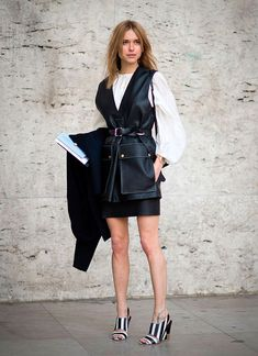 Pernille Teisbaek posa para foto de street style usando blusa bufante off white, mini saia de couro preta, colete de couro preto amarrado e sandália de listras