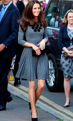 kate middleton in a grey pleated Orla Kiely dress with a pair of black satin pumps and a small box clutch