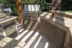 Naturekast cabinetry insets used with masonry to create a rustic outdoor summer kitchen.