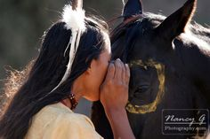 A Native American Indian boy wearing a feather is talking to his horse sharing a special moment like a horse whisperer
