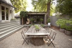 A European-style gravel courtyard in the backyard includes a dining table made using cuts from a dead oak tree as its base.