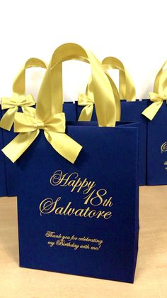 Elegant Birthday party gift bags with gold satin ribbon handles and custom names. Personalized birthday party favors make a unique way to thank guests for attending your special day. #welcomebag #personalizedgift #elegantgift #partyfavors #birthdayparty #annyversarygift #birthdaygift #giftbags #birthdaycelebration #elegantbag #30thbirthday #40thbirthday #20birthday #birthdayfavors #elegantbirthday #blueandgold