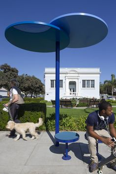 Redesigned bus shelters in Santa Monica comprising blue discs on stilts.