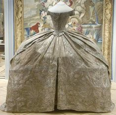 21 August 1745 Wedding-dress of Catherine II  (later known as Catherine The Great)  bridal dress sewn from silver brocade embroidered with silver thread.  This silhouette shows European fashion of the time, with narrow shoulders, a small waist and wide skirt to farthingales    An interesting feature of this particular dress is that it is the waist size of 43 centimeters.