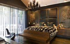 A way to warm the feeling of a room, fill in missing decor, and generally masculinize and chic up walls: dark paint and an upholstered banquette or headboard.