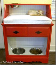 You can make your own pet center by using a base kitchen cabinet. Remove the doors, add wainscot if you like or paint it the same color.  Plywood cut to size for the top(where your cushion will go), add sides and use the shelf you took out for your top (cut hole in shelf for add'l bowl) Note: dog food at bottom, cat food bowl on top!
