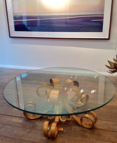An interesting wrought iron, gilt, Hollywood style coffee table, with four central legs, 80 cm diameter at widest. With glass top 110 cm diameter x 15 mm thick. Italian 1970s.