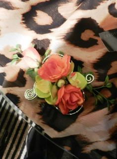 Silk Wrist Corsage Using A Single Green Orchid Accompanied By Coral Spray Roses & Accented With Greens & Light Green Wire Spirals.