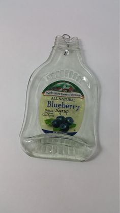 I created this hanging keepsake by slumping the bottle in the kiln with a hire fire wire hanger. the syrup label was then re-attached to the back of the bottle with sealer. Enjoy this as a serving tray for cheese, crackers, use as a soap or jewelry tray, candle holder or simply enjoy on your kitchen wall! Dimensions: 7.5 inches long, 4 inches at widest point Weight: 8.4 oz  Have a favorite bottle that youd like to see this way? Let me know