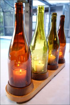 Wooden Stand Four Wine Bottle Candleholder - The colors of the glass add an ambiance great for an indoor table centerpiece, mantel display, wine bar, or a patio or porch area. The bottles sit on a wood base with wooden feet. Each bottle fits into its own individual stand. This is a great hurricane lantern because the wind won't blow these candles out. We handcraft our wood base and after we remove the bottom of the bottle we polish the glass edge smooth. Four votive candles are included.