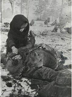 A child with his murdered mother in a concentration camp for civilians, Belarus. March 1944.