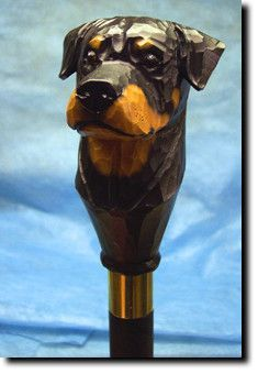 Rottweiler Dog Walking Stick. The Rottweiler Dog Walking Stick is a reproduction of an original woodcarving by Michael Park, a Master woodcarver, recognized worldwide for his detailed carvings and reproductions. Each walking stick is cast in resin and hand painted by master artists capturing a style of charm and warmth.