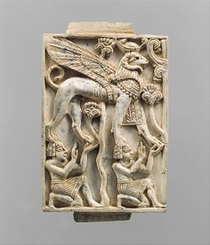 Plaque with two kneeling youths supporting a ram-headed sphinx    Period:      Neo-Assyrian  Date:      ca. 9th–8th century B.C.  Geography:      Mesopotamia, Nimrud (ancient Kalhu)  Culture:      Assyrian  Medium:      Ivory