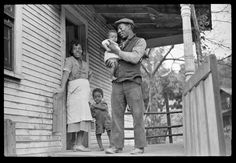 Coal miner, his wife and two of their children (note child's legs).  Bertha Hill, West Virginia.  1938.