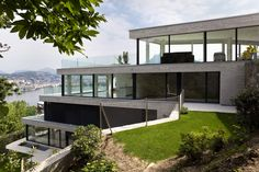 4-story white all-glass modern home cascading down the slope of a steep hill with ocean views