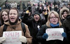 People hold placards reading 'I pray for Crimea-Ukraine' during a rally at the Independence square in central Kiev