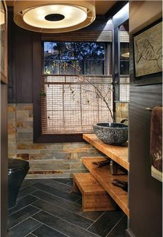 Beautiful bathroom materials. Long slate floor tiles in a chevron pattern, natural stone tiles on the lower half of the wall. Dark painted walls contrasted with light open shelves and a natural stone vessel sink.