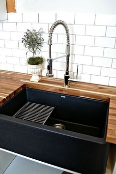 Black farmhouse sink with wood counters and white subway tile backsplash