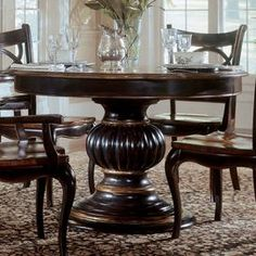 Pedestal dining table in contrasting cherry and black rub-through with an ornately detailed based.    Product: Dining tableConstruction Material: Hardwood solids with cherry, mahogany and white ash burl veneers Color: Black rub-through and rich cherry Features:   Pedestal design   Seats up to six  One  20 (included) leaf extends the table from 54 to 74  Dimensions: 30 H x 54 Diameter